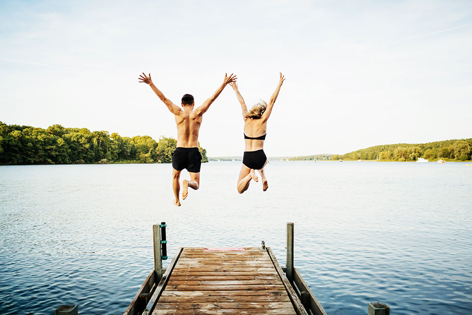 Two friends jumping with their arms in the air